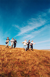 Group of teenage girls running across a field - city dwellers on field trip to countryside; UK