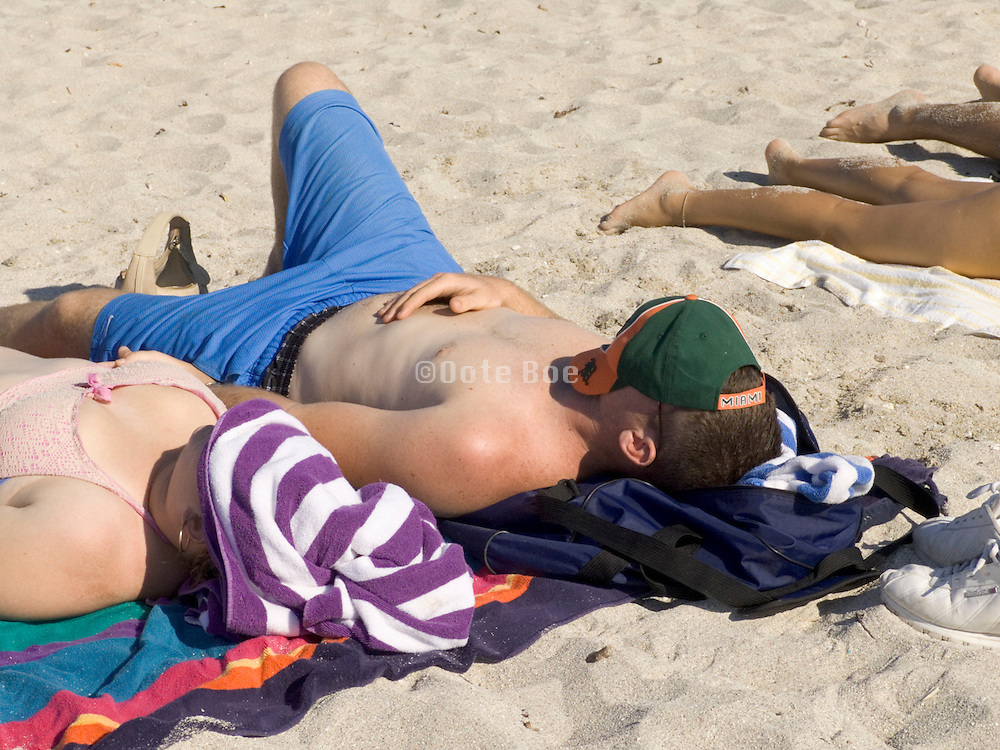 close up of sunbathers lying on beach Miami USA