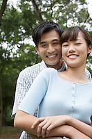 Mid adult couple embracing in park portrait