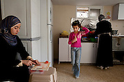 Abdul-Baset Razem's wife, Munira, tends to the makloubeh at the stove, while his daughter Mariam, 14, chops tomatoes at their extended family's home in the village of Abu Dis, East Jerusalem. (From the book What I Eat: Around the World in 80 Diets.) Their 8-year-old daughter, Maram, saunters through, escaping kitchen duties before the big weekend midday meal.