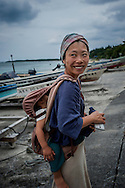 Mother and her son out for a walk on the beachfront in Fukugi, named after a waxy-leafed broadleaf tree planted throughout Okinawa as windbreaks against the numerous typhoons that lash the archipelago every year.  Near Nago, Okinawa main island, Japan.