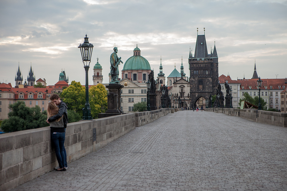 Lovers during early morning at Charles Bridge and the view to Prague Old Town during the change from night to day.