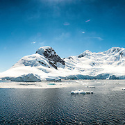 A high resolution panorama of mountains at Cuverville Island on the Antarctic Peninsula, with part of the ship in the frame at the very right.