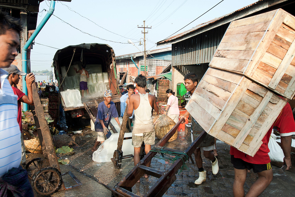 Blocks of ice are unloaded from the truck early in the morning at the Yangon fishing port in Myanmar.