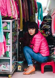 A clothes shop vendor stares at the camera, Hanoi, Vietnam, Southeast Asia