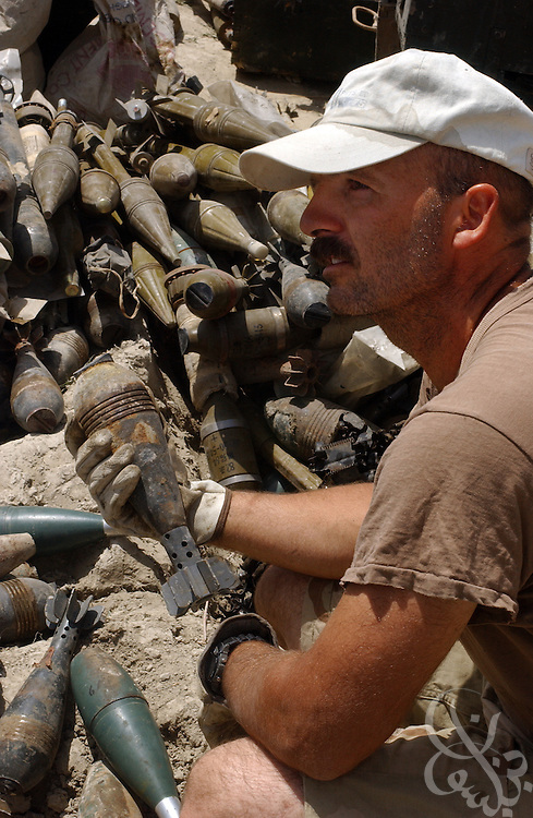 U.S. Special Forces Sgt. 1st Class Lane handles mortars from part of a recovered 30 ton al-Qaeda weapons cache that are displayed July 3, 2002 at the Khost airbase in southeastern Afghanistan. U.S. special forces in the region uncovered the weapons last week after receiving tips of al-Qaeda activity in the area.