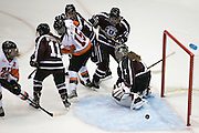 RIT's Kolbee McCrea (#15) and RIT's Morgan Scoyne try to get one past Union goaltender Shenae Lundberg during a game at the Gene Polisseni Center on October 3, 2014.