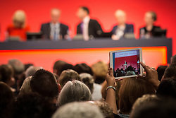 © Licensed to London News Pictures . 28/09/2015 . Brighton , UK . A member of the audience takes a photograph of JOHN MCDONALD on an iPad as McDonald , the shadow chancellor , speaks at the 2015 Labour Party Conference . Photo credit : Joel Goodman/LNP