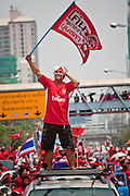 "Mar. 27, 2010 - BANGKOK, THAILAND:  A Red Shirt protestor waves their banner during a Red Shirt march in Bangkok, Saturday, March 27. More than 80,000 members of the United Front of Democracy Against Dictatorship (UDD), also known as the ""Red Shirts"" and their supporters marched through central Bangkok March 27 during a series of protests against and demand the resignation of current Thai Prime Minister Abhisit Vejjajiva and his government. The protest is a continuation of protests the Red Shirts have been holding across Thailand. They support former Prime Minister Thaksin Shinawatra, who was deposed in a coup in 2006 and went into exile rather than go to prison after being convicted on corruption charges. Thaksin is still enormously popular in rural Thailand.    PHOTO BY JACK KURTZ"
