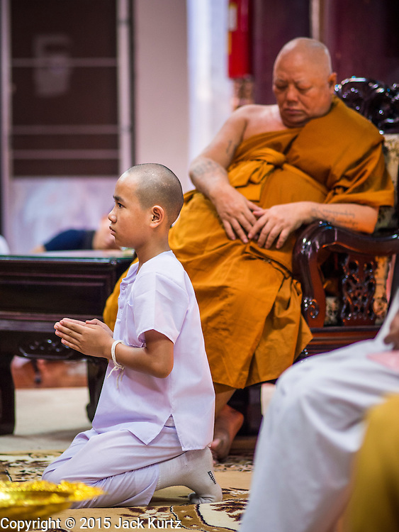 "06 APRIL 2015 - CHIANG MAI, CHIANG MAI, THAILAND:  A boy being ordained as a novice monk prays in front of a senior monk during the boy's ordination on the last day of the three day long Poi Song Long Festival in Chiang Mai. The Poi Sang Long Festival (also called Poy Sang Long) is an ordination ceremony for Tai (also and commonly called Shan, though they prefer Tai) boys in the Shan State of Myanmar (Burma) and in Shan communities in western Thailand. Most Tai boys go into the monastery as novice monks at some point between the ages of seven and fourteen. This year seven boys were ordained at the Poi Sang Long ceremony at Wat Pa Pao in Chiang Mai. Poy Song Long is Tai (Shan) for ""Festival of the Jewel (or Crystal) Sons.  PHOTO BY JACK KURTZ"