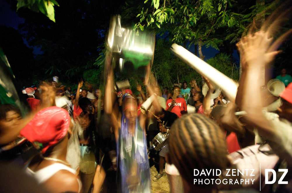 Members of one of many rara bands present at the voodoo festival at Saut D'eau dance on a a dark street while playing their traditional form of raucous music performed with homemade instruments on July 14, 2008. The bands march and play throughout the town day and night during the 3-day festival in central Haiti.