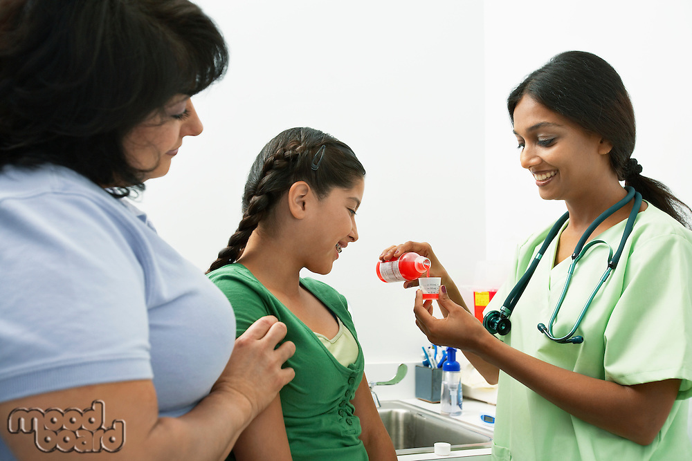 Female doctor pouring medicine for girl