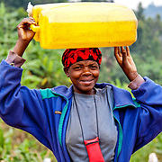 Uwamaliya Delphine carries a jerry can of water back to her home in Kisaro, Rulindo District, Rwanda.