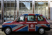 A traditional London Hackney carriage taxi cab advertising Vodafone, a multi-national mobile communication business.