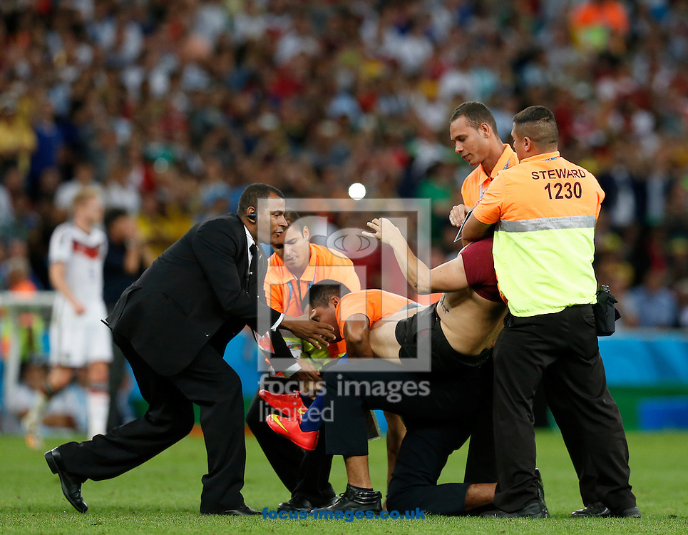 Stewards restrain a pitch invader during the 2014 FIFA World Cup Final match at Maracana Stadium, Rio de Janeiro<br /> Picture by Andrew Tobin/Focus Images Ltd +44 7710 761829<br /> 13/07/2014
