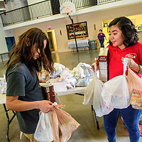 Family, Career & Community Leaders of America volunteers Marcus Sena, left, and Jazmine Brown collect bags of groceries to deliver to community members at the First Baptist Church in Grants Thursday.