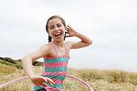 Smiling pre-teen Girl Hula Hooping in field