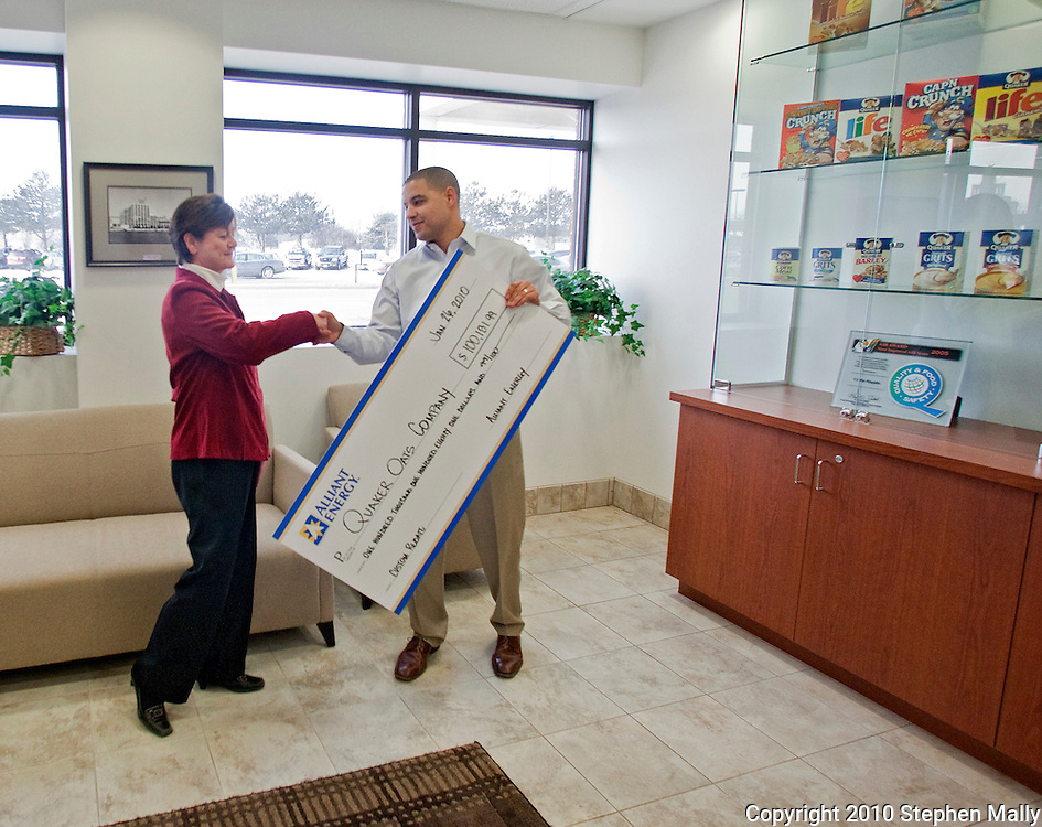 Alliant Energy's Chad Wiltz (right) shakes hands with Quaker Oats' Kay Driscoll as Quaker Oats receives a rebate check from Alliant Energy at Quaker Oats in Cedar Rapids, Iowa on Tuesday January 26, 2010. (Stephen Mally for Quaker Oats)