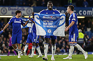 Kurt Zouma of Chelsea holds up a banners saying 'We're On Our Way to Wembley' after the Capital One Cup Semi Final 2nd Leg match between Chelsea and Liverpool at Stamford Bridge, London, England on 27 January 2015. Photo by David Horn.
