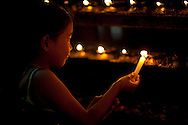 Young girl gives an offering by lighting butter candles in a Hindu Temple, Durbar Square, Kathmandu, Nepal