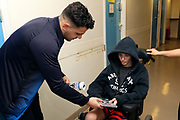 AFC Wimbledon attacker Egli Kaja (21) handing over a copy of a Football Manager game delivering Christmas presents to the children on behalf of AFC Wimbledon, at St George's Hospital, Tooting, United Kingdom on 13 December 2018.