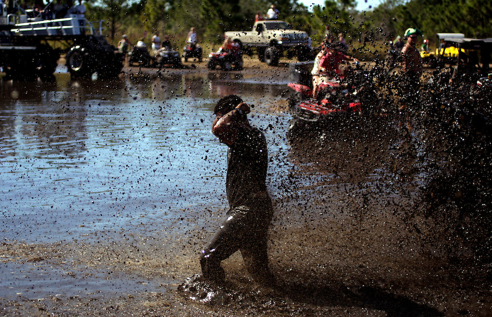 A reveler is splashed with mud after retreiving his sunglasses from the bottom of a mud pit at the Redneck Yacht Club in Punta Gorda, Fla. Photo by: Greg Kahn