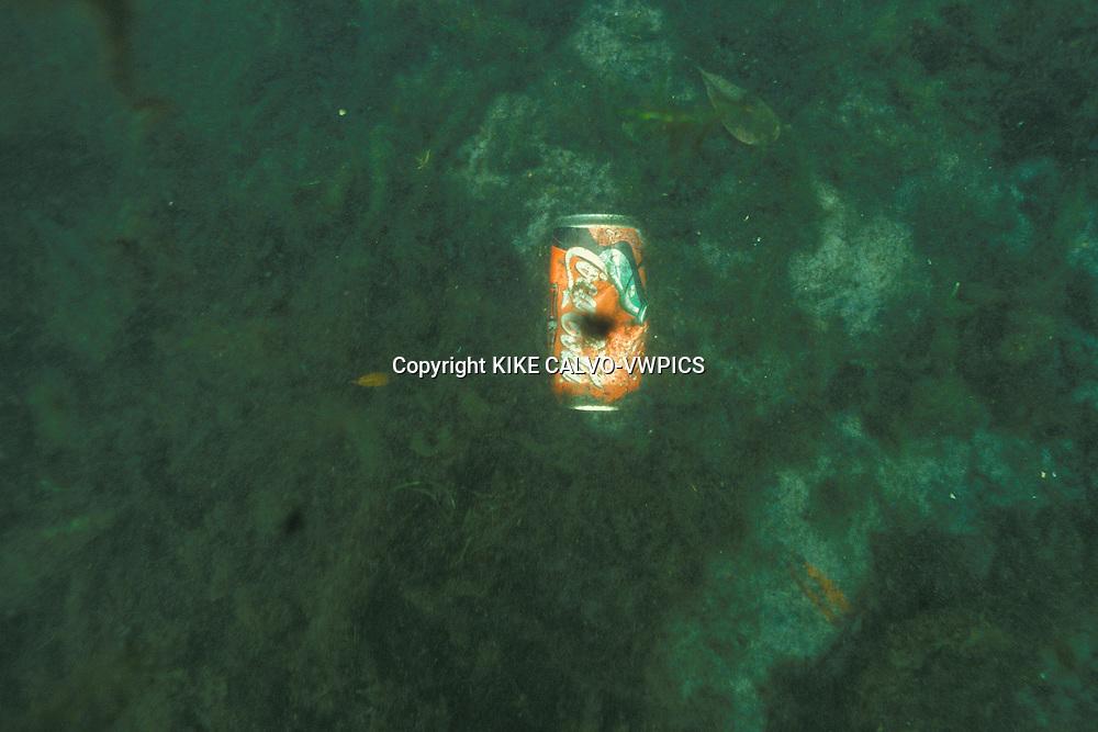 Coke can underwater in the ocean floor.