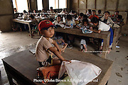 A boy sits on the desk of Nang Chanton, his mother, who is a teacher at Ban Buamlao Primary School in Ban Buamlao, Laos. Because daycare programs are scarce in Laos, Ms. Chanton is accompanied to her job each day by her son.