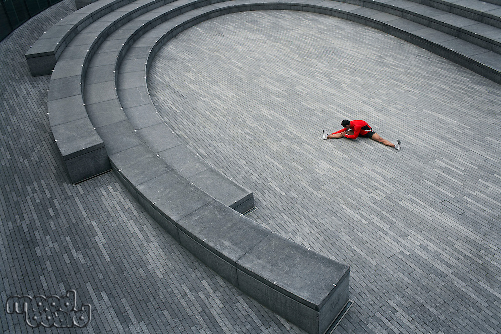 Man stretching in the Scoop amphitheatre London England elevated view