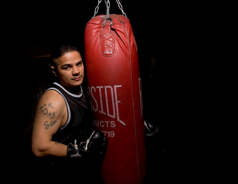 Gary Gomez, holds the WBC Continental Americas belt, which he won in December. Here he poses at his gym in West Valley City where he helps teach boxing to young family members and friends. Feb. 12, 2005. August Miller/ Deseret Morning News DIGITAL PHOTOGRAPH