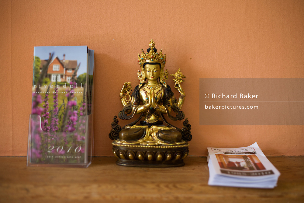 Buddha icon and brochures on ledge at the Rivendell Buddhist Retreat Centre, East Sussex, England.