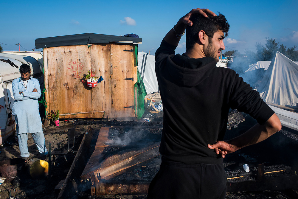 Two refugees react after returning to find their home burned to the ground at The Jungle refugee camp on October 25, 2016 in Calais, France.