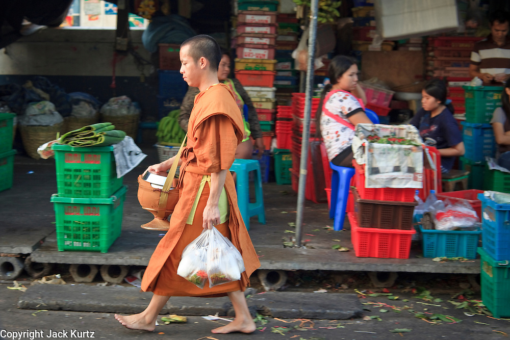 """Mar. 9, 2009 -- BANGKOK, THAILAND: A monk walks in the flower and produce market on the Chao Phraya River in Bangkok. Every morning, flowers and produce from the provinces arrive in the market where they are bundled and sold at retail in Bangkok's consumer markets. Many of the flowers are sold in and around the Buddhist temples in Bangkok. People buy them as offerings or to """"make merit."""" Photo by Jack Kurtz / ZUMA Press"""