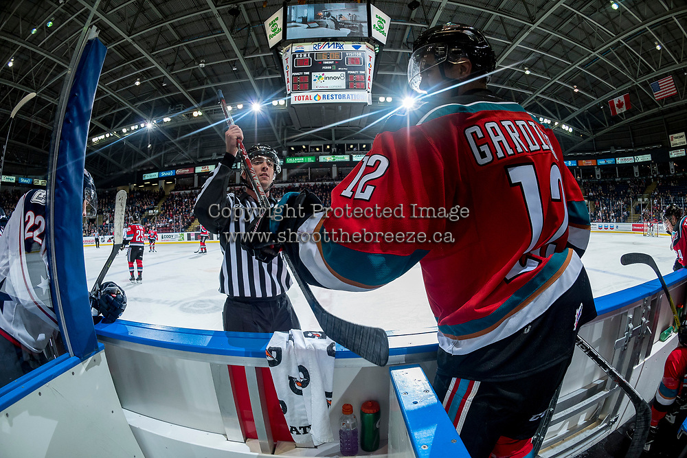 KELOWNA, CANADA - OCTOBER 27: Linesman Tim Plamondon returns a stick to Erik Gardiner #12 of the Kelowna Rockets on the bench against the Tri-City Americans on October 27, 2017 at Prospera Place in Kelowna, British Columbia, Canada.  (Photo by Marissa Baecker/Shoot the Breeze)  *** Local Caption ***