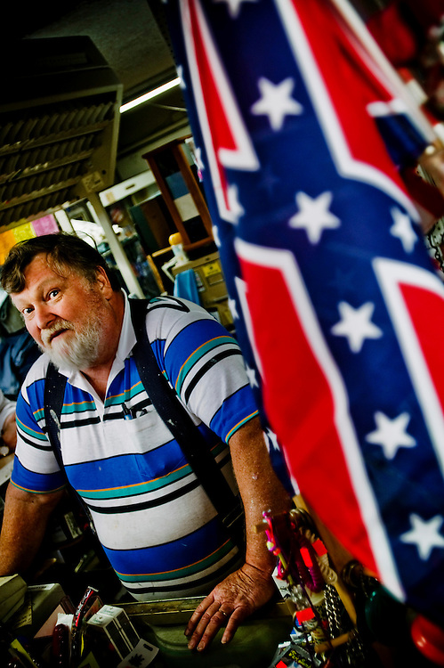 """John XX, owner of """"John's Music Store"""" where he sells everything from musical instruments, to guns to confederate flags...Photographer: Chris Maluszynski /MOMENT"""