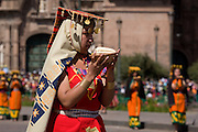 "A Virgin of the Sun holding an offering of maize to the sun. Inti Raymi ""Festival of the Sun"", Plaza de Armas, Cusco, Peru."