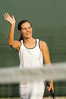 Tennis Player standing near net arm raised and Waving