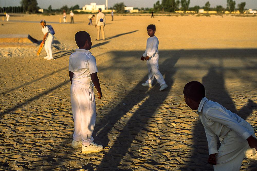 Dubai, United Arab Emirates. Boys attend a cricket camp in the desert