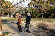 senior couple photographing first tree blossom Japan