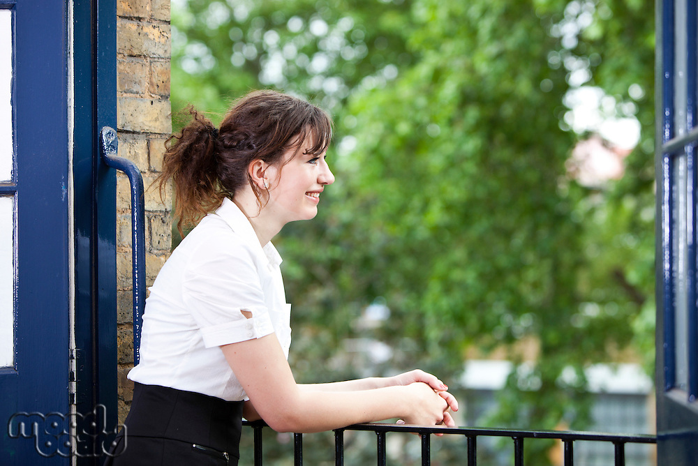 Happy young businesswoman leaning on railing while looking away