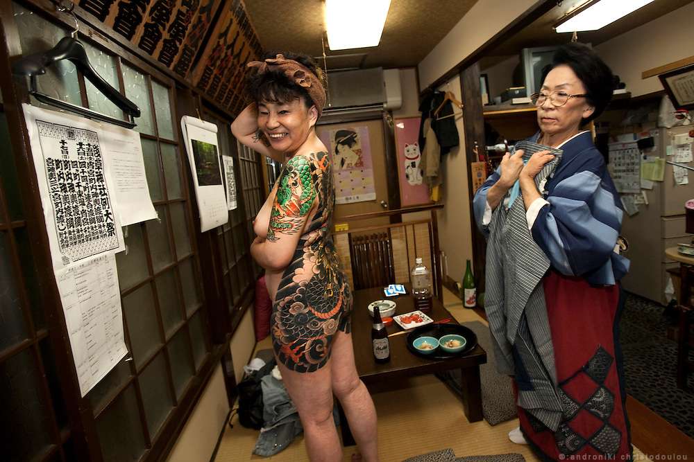 Toyomi Tamura displaying her tattoos in a small izakaya (traditional Japanese restaurant) in Asakusa.