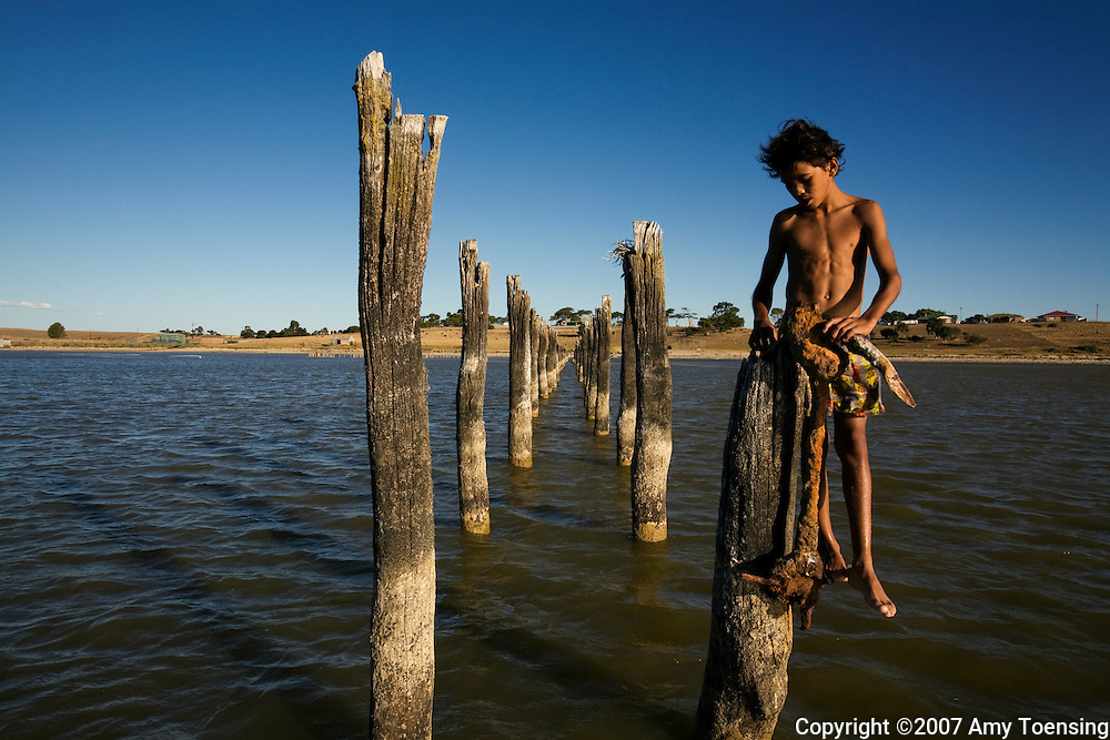 MENINGIE, SA, AUSTRALIA - MARCH 04: Kids from the Raukkan, Njarainjari Aboriginal Community make their way to deeper water in a quickly receding Lake Albert March 4, 2008 in Meningie, South Australia, Australia. Water levels are down by a foot and a half and expected to continue. Locals have never known the lake to be this low. The Murray-Darling Basin has been plagued with severe drought since the late 1990s and many growers and policy makers are being forced to find and implement more efficient irrigation systems. (Photo by Amy Toensing/ Reportage by Getty Images). _________________________________<br /> <br /> For stock or print inquires, please email us at studio@moyer-toensing.com.