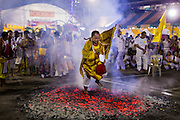 01 OCTOBER 2014 - BANGKOK, THAILAND: A man runs through the fire pit during the firewalking ceremony at Wat Yannawa (also spelled Yan Nawa) during the Vegetarian Festival in Bangkok. The Vegetarian Festival is celebrated throughout Thailand. It is the Thai version of the The Nine Emperor Gods Festival, a nine-day Taoist celebration beginning on the eve of 9th lunar month of the Chinese calendar. During a period of nine days, those who are participating in the festival dress all in white and abstain from eating meat, poultry, seafood, and dairy products. Vendors and proprietors of restaurants indicate that vegetarian food is for sale by putting a yellow flag out with Thai characters for meatless written on it in red.     PHOTO BY JACK KURTZ