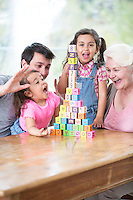 Happy multi generation family with arranged building blocks at table in house
