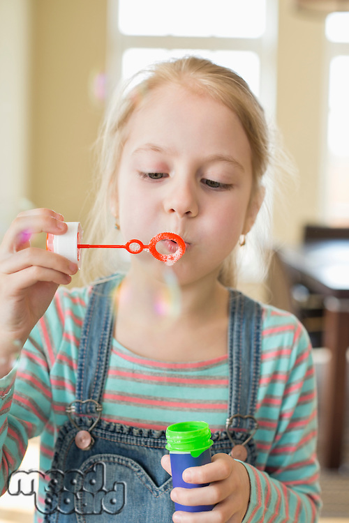Cute girl playing with bubble wand at home