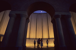 Stock photo of people standing inside the waterwall fountain in Houston Texas