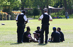 © Licensed to London News Pictures. 19/05/2020. London, UK. Police officers speak with a group of people in Chestnuts Park, north London, who are not observing social distancing guidelines. The government has relaxed the rules on the COVID-19 lockdown, allowing people to spend more time outdoors whilst following social distancing guidelines. Photo credit: Dinendra Haria/LNP