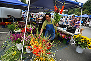 20120817    Jefferson Herr of Herr Fresh Flowers prepares a bouquet for one of his customers.<br />      Sidewalks wind through the area behind Main Street's businesses providing the perfect place for a farmers market. The year-round Davidson Farmer's Market is not only about food, it is a community gathering place as well.<br /> photo by Laura Mueller<br /> www.lauramuellerphotography.com