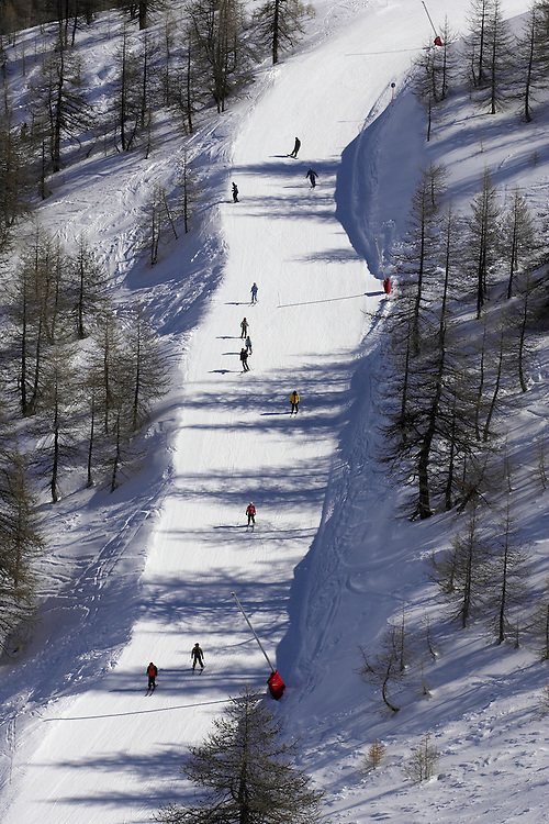 A group of skiers and snowboarders on a piste in Serre Chevalier, France