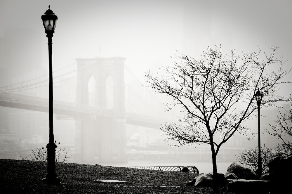 The Brooklyn bridge in the fog seen from the Empire Fulton Ferry State Park in DUMBO, Brooklyn, New York.